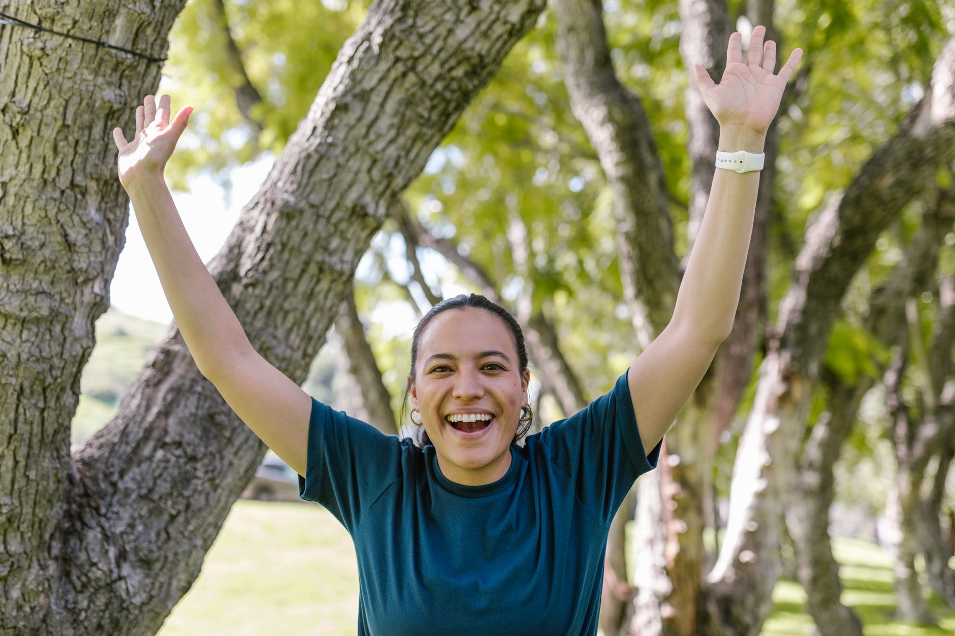 smiling woman in blue crew neck t shirt raising her hands